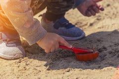 Baby ` s Hände im Sand, Baby, das im Sand spielt Stockbild