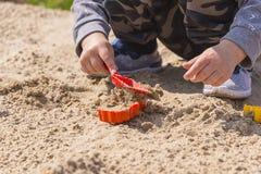 Baby ` s Hände im Sand, Baby, das im Sand spielt Stockfotografie