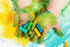 Baby ` s Hände mit bunten Pastellkreiden Lizenzfreies Stockfoto
