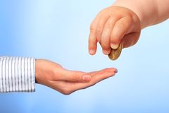 Baby's hand and coin. Stock Photo