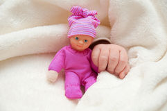 Baby's hand with doll Royalty Free Stock Photos