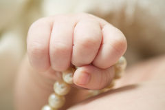 Baby's hand holding pearls Royalty Free Stock Images