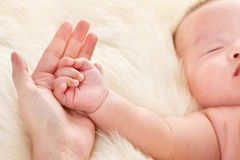 Baby's hand on mother's palm Stock Photo