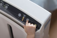 The baby`s hand pressing the power button on the air purifier to clean up the polluted air stock image