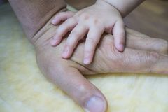 Baby`s hands on grandfather`s hand stock photography