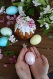 Easter egg in the hands of a child and a cake in sugar icing. Baby`s hands hold easter egg. Easter egg in the hands of a child. Easter egg in the hands of a royalty free stock photo