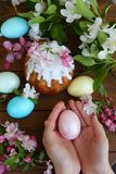 Easter egg in the hands of a child and a cake in sugar icing. Baby`s hands hold easter egg. Easter egg in the hands of a child. Easter egg in the hands of a stock image