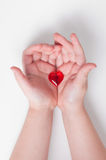Baby's hands with a little heart. Baby girl's hands handing little glossy heart royalty free stock photos