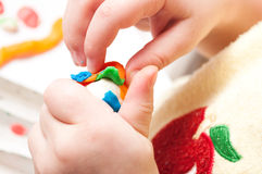 Baby's hands with plasticine. Child moulds from plasticine on table. hands with plasticine Stock Photography
