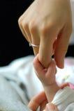 Baby's holding mum's finger Stock Images