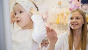 Baby ` s Kleiderspeicher - kleines blondes Baby mit der Mutter, die Einkaufs- und des Kaufenshübschen Hut tut Stockfotos