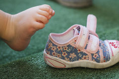 Baby's leg and shoe Stock Image