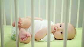 Baby Lying in a Crib at Home Eating its Fingers Royalty Free Stock Image