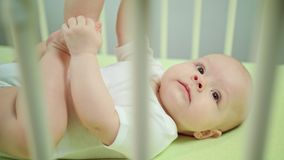 Baby Lying in a Crib and Playing. Baby`s lying on a green linen in a crib at home and playing. Soft focus close-up Stock Image