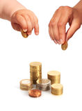 Baby's and mothers' hands with coins. Royalty Free Stock Image