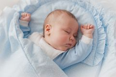 Baby`s restful sleep. Newborn baby in a wooden crib. The baby sleeps in the bedside cradle. stock photo
