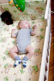 Baby`s restful sleep. Newborn baby in a wooden crib. The baby sleeps in the bedside cradle. Safe living together in a bedside cot. The little boy dozed off royalty free stock photography