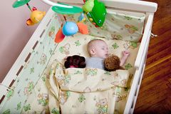 Baby`s restful sleep. Newborn baby in a wooden crib. The baby sleeps in the bedside cradle. Safe living together in a bedside cot stock photo