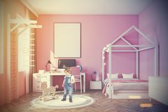 Baby s room with a computer, pink toned. Nursery with pink walls, a wooden floor, a double bed with a house like roof, a computer desk and a ladder. A framed Royalty Free Stock Photos