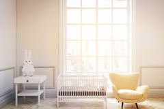 Baby`s room with a large window, toned. Front view of a baby`s room interior with a cradle, an armchair and a bedside table. There is a large window with a Royalty Free Stock Photos