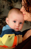 Baby's Security. Baby taking comfort in his mother's touch Stock Photography
