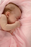 Baby's Security Blanket. Sleeping baby pulling cover to her face Royalty Free Stock Image