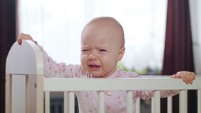Baby Standing in a Crib at Home. Crying. Baby`s standing in a white crib at home and crying. Medium shot Royalty Free Stock Photos