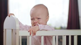 Baby Standing in a Crib at Home. Crying. Baby`s standing in a white crib at home and crying. Medium shot Royalty Free Stock Images