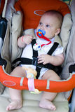 Baby in Safety Car Seat. A young baby strapped into a safety harness in a car seat Royalty Free Stock Image