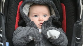 Baby in safety car seat. Baby boy sitting in a car seat, he is protected by seatbelts stock video