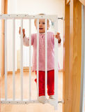 Baby with safety gate of  stairs. Little baby standing on safety gate Stock Photos