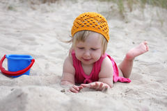 Baby on sand. Baby girl lying in sand and playing with sand Royalty Free Stock Images