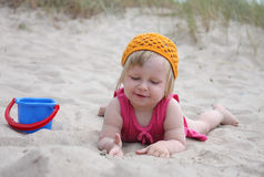 Baby on sand. Baby girl lying in sand and playing with sand toys Royalty Free Stock Photography
