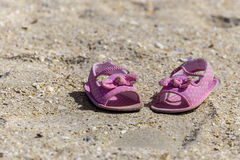 Baby sandals on the beach Royalty Free Stock Images