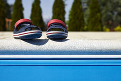 Baby sandals at the edge of swimming pool. Pair of baby sandals at the edge of swimming pool at sunny day stock images