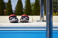 Baby sandals at the edge of swimming pool Royalty Free Stock Photos