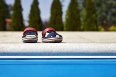 Baby sandals at the edge of swimming pool. Pair of baby sandals at the edge of swimming pool at sunny day stock image