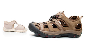 Baby sandals standing opposite male shoes, isolate Stock Image