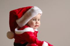 Baby Santa. A little caucasian white girl child portrait with cute expression in her face dressed like Santa Claus wearing a red hat and costume, looking to the Royalty Free Stock Photos