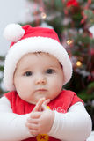 Baby santa. Baby in Christmas bonnet looks at camera Royalty Free Stock Photo