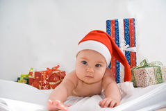 Baby Santa Claus. Baby in Santa Claus hat and some gifts Royalty Free Stock Photos