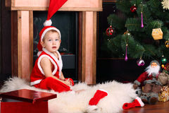 A baby in the Santa Claus' clothing Stock Photo