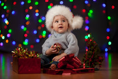 Baby in Santa Claus hat on festive background. Funny baby in Santa Claus cap on bright festive background Stock Images
