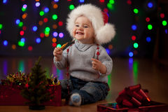 Baby in Santa Claus hat on festive background. Funny baby in Santa Claus cap on bright festive background Royalty Free Stock Image