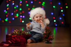Baby in Santa Claus hat on festive background. Funny baby in Santa Claus cap on bright festive background Royalty Free Stock Photography