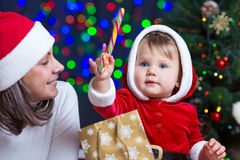 Baby Santa Claus with mother near Christmas tree Royalty Free Stock Images