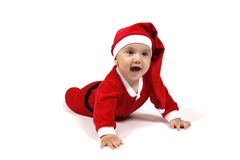Baby in Santa Claus suit. Close up of cute baby lying on ground dressed in Santa Claus outfit, isolated on white background Royalty Free Stock Photo