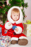 Baby in Santa costume at the Christmas tree Royalty Free Stock Image