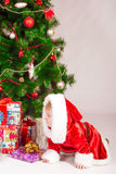Baby in Santa costume at the Christmas tree Royalty Free Stock Photos