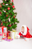 Baby in Santa costume at the Christmas tree Royalty Free Stock Photography